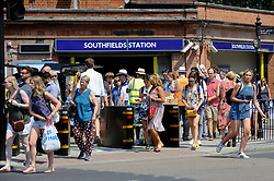 © Licensed to London News Pictures. 06/07/2018. LONDON, UK. Spectators make their way to the Wimbledon Tennis Championships from the nearest tube station, Southfields.  Temperatures forecast to approach 30C mean that the majority have taken precautions to protect themselves from the sun by wearing sunglasses and sunhats.  Photo credit: Stephen Chung/LNP