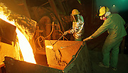 29 JANUARY 1999  - EL PASO, TEXAS: Manny Barrios, left, a refiner at the Asarco copper smelter in El Paso, Texas, and Joe Raigoso, a lugman, at the smelter, skim molten copper coming out of the furnace at the smelter. Asarco mothballed the smelter for at least three years because of low prices in the copper industry. In mid 1997, copper was selling for approximately $1.20 per pound, it is currently selling for about .65 cents per pound, forcing copper producers like Asarco to take drastic belt tightening measures. About 370 workers were laid off as the plant's machinery was mothballed. Closure of the Asarco smelter comes on the heels of the closure of copper mines in southern New Mexico owned by the Phelps-Dodge company, an Asarco competitor. Asarco officials have said they may reopen the plant if copper prices rebound. Photo by Jack Kurtz / ZUMA Press