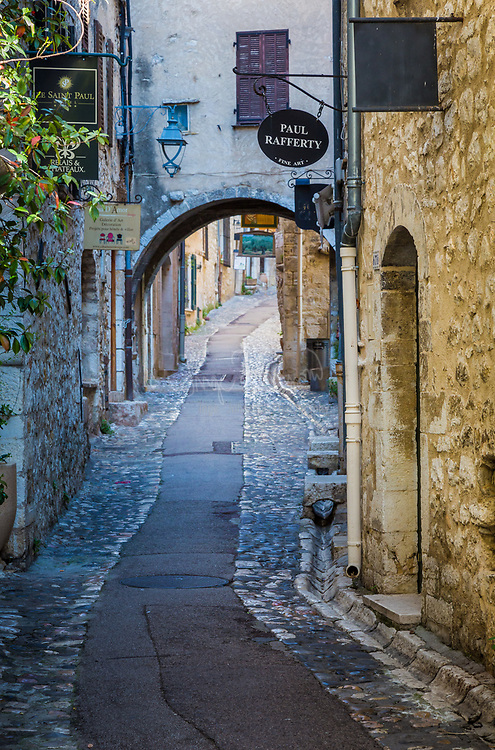 """Rue Grande street in Saint Paul de Vence in France.<br /> -----<br /> Saint-Paul or Saint-Paul-de-Vence is a commune in the Alpes-Maritimes department in southeastern France. One of the oldest medieval towns on the French Riviera, it is well known for its modern and contemporary art museums and galleries such as Fondation Maeght which is located nearby. It was probably between the 10th and 12th century that a settlement formed around the ancient church of Saint Michel du Puy to the south, and near the castle on the highest part of the hill. In the Middle Ages, the region was administered by the Counts of Provence. In the 13th century, Count Charles II granted more privileges to St. Paul, including the right to hold a weekly market. At the beginning of 14th century, St. Paul acquired more autonomy and became a prosperous city of merchants and nobility. In 1388, the County of Nice broke off from Provence to reattach itself with the states belonging to the Count of Savoy. These new circumstances gave St. Paul a strategic position: the city becomes a border stronghold for five centuries. St. Paul went through its first fortification campaign in the second half of 14th century: the north gate of the city, called """"Porte de Vence,"""" dates back to the medieval wall. At the time of the wars of Italy, Provence was invaded twice by the troops of Charles V. Considering the low side of the border of Provence and the obsolescence of the medieval fortifications in Saint-Paul, Fran�ois 1st decided in 1538 to build the new city walls, able to withstand the power of the artillery. This fortified wall, built between 1543 and 1547, is preserved in its entirety. On its northern and southern fronts four solid bastions protect both the city gates. In the 17th century, Saint-Paul experienced a religious period through the influence of Antoine Godeau, Bishop of Vence. The church was elevated to college, and was expanded and embellished. St. Paul also saw an urban revival thanks to the famili"""
