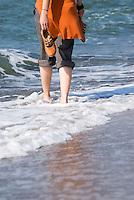 Female walking in waves along Baltic coast