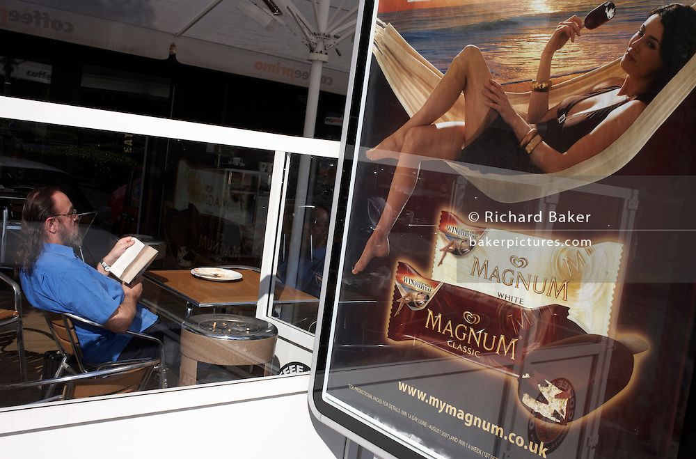 Following UK commercial driving law, a lorry driver relaxes by reading in a window at the M40 motorway services in Warwickshire, England. Leaning back while engrossed in his book, the man is sitting in sunlight on this summer's day. Outside is a poster advertising the premium ice cream brand, Magnum. A girl is shown also lounging about enjoying a Magnum on a beautiful sun-kissed beach, with the sun reflecting on a calm sea. We see Magnum's web site and their products of Classic and White chocolate snacks in their wrappers. The man is oblivious to the nature of the ad but it lends a sense of paradise versus reality, between the fantasy of youth, natural beauty and the reality of an older working man on the road.