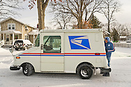 Merrick, New York, U.S. January 3, 2014. A United States Postal Service USPS truck and mail carrier deliver mail as a dangerous deep freeze settles in, after a blizzard dumped 6-12 inches of snow on Long Island. The temperature range is 13 to 18 degrees Fahrenheit (-11° to -8° Celsius), with wind gusting up to 45 mph. Wind chill factors make it between 5° F to -10° F (-15° to -23° C), with record lows expected at night.