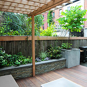 Modern Garden featuring traditional stacked stone seating wall and Cedar pergola with planting for seasonal interest by Outside Space NYC