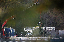 A crane moves part of the wreckage from the helicopter crash at Leicester City Football Club.