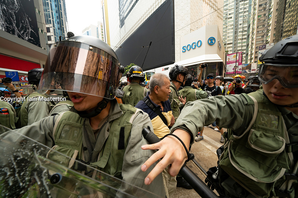 Hong Kong. 29 September, 2019. Illegal march by thousands of pro-democracy supporters from Causeway Bay to Government offices at Admiralty is under way. Police unsuccessfully tried stop march at start with teargas fired and scuffles. March marks the 5th anniversary of the start of the Umbrella Movement. Pic. Crowd attack police who have arrested a man. Iain Masterton/Alamy Live News.