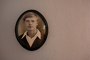 A portrait of a young man D. at 18, is on the wall in his bedroom. He was born in the former Soviet Union, where his father was a teacher. At that time, it was conventional for him, both as a teacher and as a father, to use physical violence to raise children. When D. became a father by himself, he initially saw physical violence as a natural upbringing method for his children. <br />Before the collapse of the Soviet Union, he immigrated to Germany, and this movement to Germany brought a significant change in his life. Old values and norms had to be questioned ultimately. He had to learn a new language. He also quickly knew that violence against children should never be part of upbringing. He learned to speak and to discuss with his children instead of using physical violence.