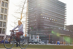 Teenage girl riding a bicycle in city, Munich, Bavaria, Germany