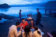 Friends sit down for food together beside Lugu Lake in the blue dusk light, Yunnan Province, China.