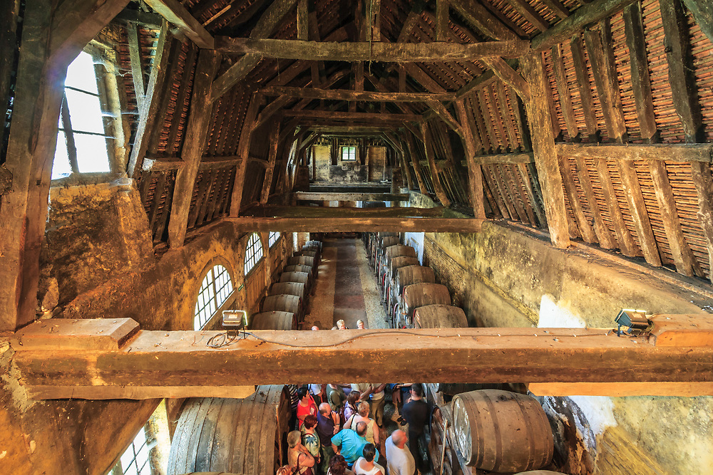 A tourist group gets to know about calvados in the cellars of Château du Breuil in Normandy, France. The complex exchanges between air, wood, and alcohol give Calvados its soft flavor and bouquet.