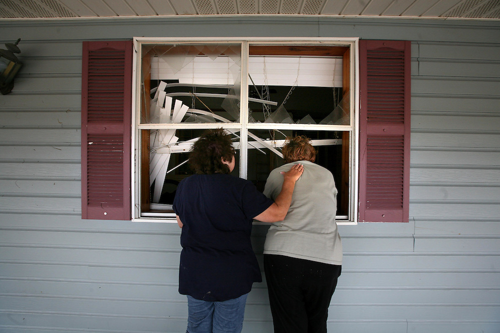 Betty Adkins, left, comforts Lois Berg as the two look in on Lois's house for the first time after Hurricane Ike in Sabine Pass Friday September 19, 2008.