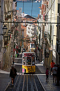 As a local leans out from a window above and others walk uphill, one of the two cars of the funicular railway climbs the steep gradient of on Rua de Bica de Duarte Belo Elevador da Bica, on 13th July 2016, in Bairro Alto district, Lisbon, Portugal. The mechanical motor of the elevator was installed in 1890, but the lift only began functioning on 28 June 1892, after a couple of years of tests. The Bica Funicular is a funicular railway line in the civil parish of Misericórdia, in the municipality of Lisbon, Portugal. It connects the Rua de São Paulo with Calçada do Combro/Rua do Loreto, operated by Carris.