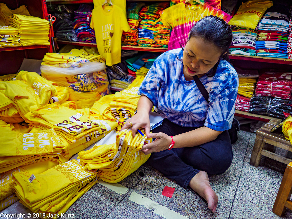 """03 JULY 2018 - BANGKOK, THAILAND: A shop keeper in Bobae Market in Bangkok inventories yellow shirts that say """"Long Live the King."""" The birthday of King Maha Vajiralongkorn Bodindradebayavarangkun, Rama X, is 28 July. The King, the only son of Thailand's late King Bhumibol Adulyadej, became the King of Thailand in 2016 after the death of his father. King Vajiralongkorn was born on 28 July 1952, a Monday. In Thai culture each day of the week has a color, and yellow is the color is associated with Monday, so people wear yellow for the month before his birthday to honor His Majesty.     PHOTO BY JACK KURTZ"""