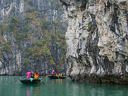 Asia, Viet Nam, Bái Tu Long Bay, Bái Tu Long National Park. Sightseeing tourists in a rowboat on the bay. Cliffs over the water.