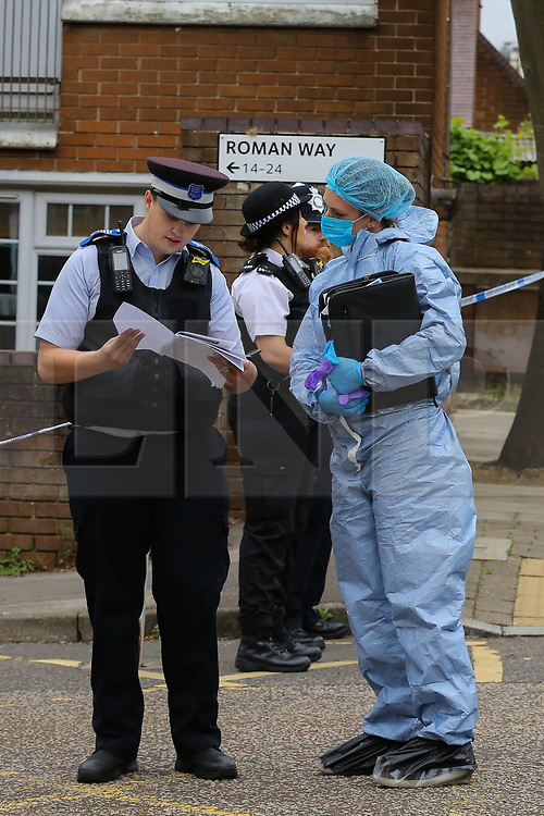 © Licensed to London News Pictures. 04/07/2020. London, UK. Police officer speaks with a forensic officer on Roman Way, Islington in north London as police launch a murder investigation following fatal shooting. Police were called at at 3.20pm to Roman Way, following reports of shots fired.  Officers attended with LAS and found a man, believed to be aged in his early 20s, suffering from gunshot injuries. Despite their best efforts, he was pronounced dead at the scene. Photo credit: Dinendra Haria/LNP