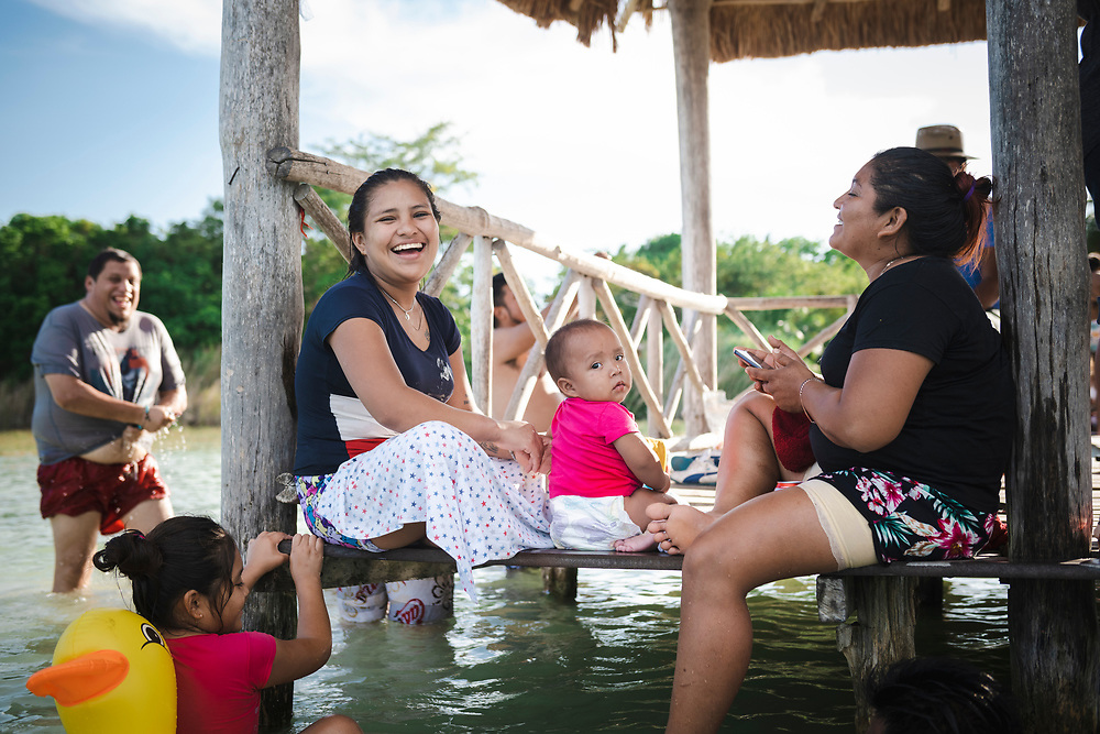 Bacalar, Mexico - June 2, 2021: People enjoy a sunny afternoon at Bacalar Lagoon on the public dock at the end of Calle 36. Bacalar is located several miles from the border with Belize.