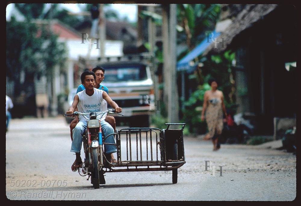 Teenagers drive motorbike version of a pickup truck down quiet side street of downtown Krabi. Thailand