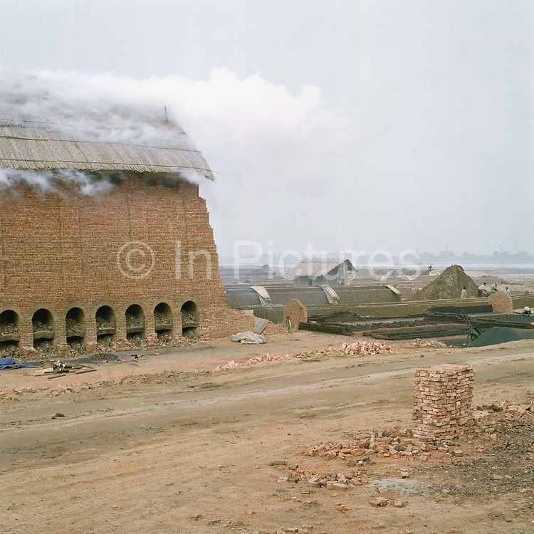 Brick kilns, Dai Trach village, Bach Ninh province, Vietnam. Brick kilns have been sited along the Duong river for over a hundred years. They are usually located by rivers, not only to enable clay extraction directly from the river bed but also for transport by boat to where they are needed. Only men make bricks and usually it is the women who do the back breaking job of loading and unloading the brick kilns.