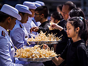 26 OCTOBER 2017 - BANGKOK, THAILAND:  People pick up sandalwood flowers they will leave as offerings during the funeral ceremony for Bhumibol Adulyadej, the Late King of Thailand. The king died on 13 October 2016 and was cremated 26 October 2017, after a mourning period of just over one year. The revered monarch was the longest reigning king in Thai history and is credited with guiding Thailand through the turbulent latter half of the 20th century.   PHOTO BY JACK KURTZ