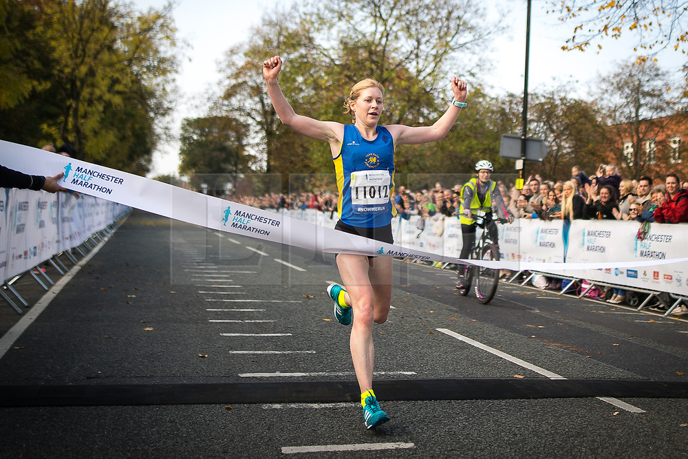 © Licensed to London News Pictures . 15/10/2017 . Manchester , UK . Women's winner REBECCA HILLAND breaks the tape at the finish line in the Greater Manchester Half Marathon in Old Trafford . Photo credit : Joel Goodman/LNP