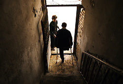Amira Khalid, 44, helps her husband, Salah Izat, 51, down the stairs of their home, Baghdad, Iraq, March 2, 2004. Izat's home was destroyed in March 2003 when an American missile hit just outside their front door. A year later, Izat is getting better pay wages, but has lost his right leg from diabetes. He says the lack of medical resources after the war made him unable to get proper attention for his ailing leg, possibly being the reason it became so gangrenous that it had to be amputated.