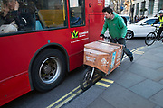Delivery cyclist battling past a bus many times his size through the busy traffic in London, England, United Kingdom. (photo by Mike Kemp/In Pictures via Getty Images)