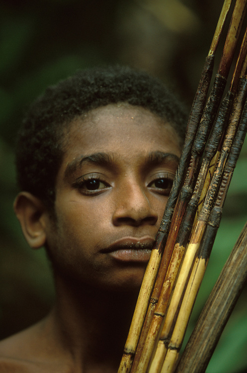 A young Kombai boy with decorated bow and arrows in Papua, Indonesia. September 2000. The Kombai are a so-called treehouse people who build their homes high up in the trees.