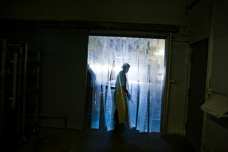 Eduardo Leon, a Mexican immigrant from Puebla now living in Swan Lake, stands in a passageway holding out the blade he uses to cut out the duck livers at Hudson Valley Foie Gras in Ferndale, New York on October 12, 2008.