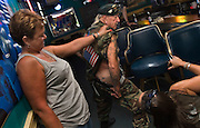 "YOUR NAME.""I have your name on a tattoo on my right buttock,"" said Veteran Elton Ensor, 82, to one of the ladies he just met as they take a peek at his special tatoo that read ""Your Name"" inked just below his waist, while on a beer break at a karaoke bar in Fort Washington, Md. The three are one of thousands of bikers and non-riders participating in an annual motorcycle rally in the nation's capitol during the Memorial Day weekend as a show of support for the United States Armed Forces and the MIA/POW cause."