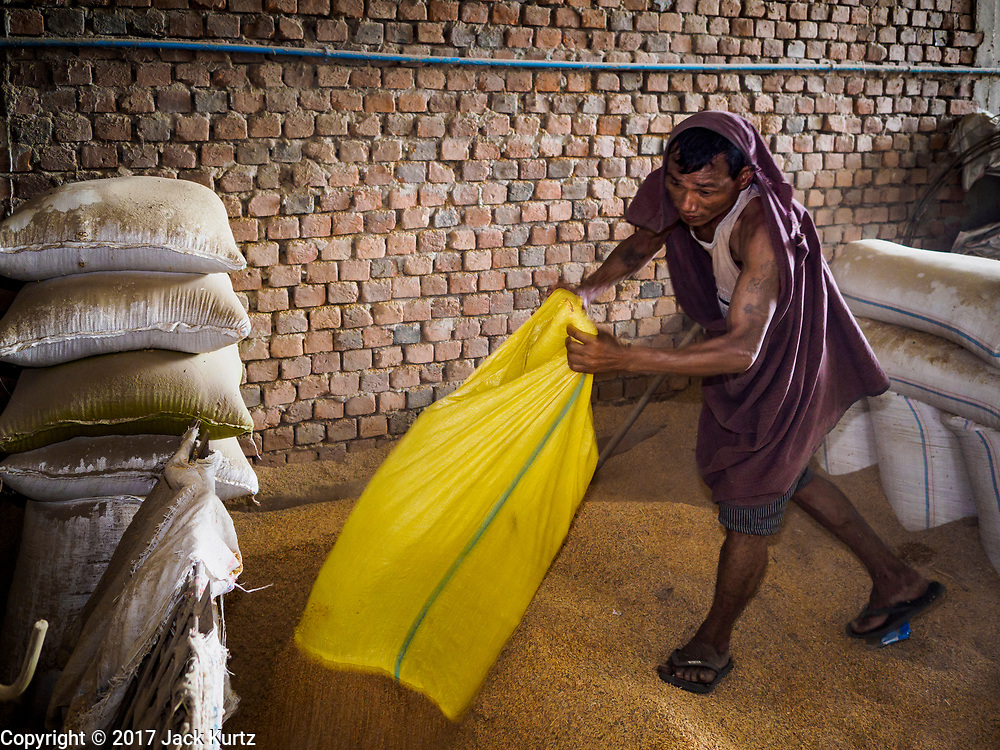 """21 NOVEMBER 2017 - WAKEMA, AYEYARWADY REGION, MYANMAR:  Workers feed sacks of paddy rice (paddy rice is unprocessed rice) into a processing line at a rice mill in the Ayeyarwady  Delta. Myanmar is the world's sixth largest rice producer and more than half of Myanmar's arable land is used for rice cultivation. The Ayeyarwady Delta is the most important rice growing region and is sometimes called """"Myanmar's Granary."""" The UN Food and Agriculture Organization (FAO) is predicting that the 2017 harvest will increase over 2016 and that exports will surge to 1.8 million tonnes.  PHOTO BY JACK KURTZ"""