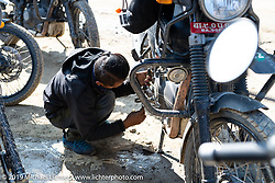 Motorcycle Sherpa mechanic does a roadside fix while on the Ride to the Heavens motorcycle adventure in the Himalayas of Nepal. This first day of riding took us from Kathmandu to Nuwakot. Monday, November 4, 2019. Photography ©2019 Michael Lichter.