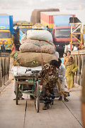 A rickshaw driver pulls his heavy load up the gangplank after disembarking from a ferry on the southern shore of the Karnaphuli River, Chittagong, Bangladesh