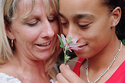 Portrait of lesbian couple standing together smelling flower,