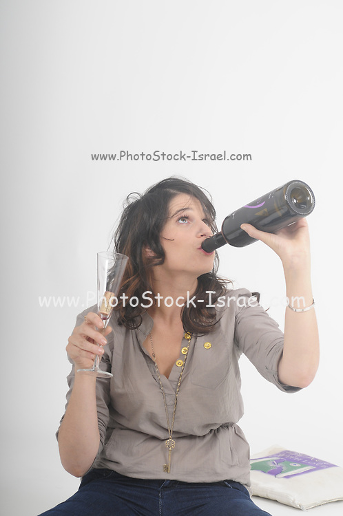 young woman prefers drinking her red wine straight out of the bottle for quicker and cleaner results studio shot on white background