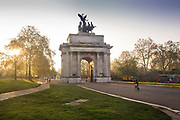 Wellington Arch, a 19th-century memorial arch topped by a bronze sculpture, Hyde Park Corner on 16th April 2020 in London, United Kingdom. Normally crowded with people London is like a ghost town as workers stay home under lockdown during the Coronavirus pandemic. During the second half of the 1820s, the Commissioners of Woods and Forests and the King resolved that Hyde Park, and the area around it, must be renovated to the extent of the splendour of rival European capital cities, and that the essence of the new arrangement would be a triumphal approach to Buckingham Palace. Changes to the road layout in the 1990s reinstated a route between Hyde Park and the Green Park for pedestrians, cyclists and horseriders using surface-level crossings.