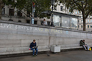 A man uses his laptop beneath the slogan Live Simply and Live in Peace has been written on a wall by an environmental activist protesting about Climate Change during an occupation of Trafalgar Square in central London, the third day of a two-week prolonged worldwide protest by members of Extinction Rebellion, on 9th October 2019, in London, England.