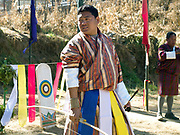 A Bhutanese man wearing a traditional 'gho' at an archery tournament, Thimphu, Western Bhutan. 'Datse' (archery) is Bhutan's national sport and is played wherever there is enough space and remains the favourite sport for all ages. There are archery tournaments held throughout the country. The targets are placed 140m apart. If the contestant hits his target, his team mates will perform a slow dance and sing his praises, while he slips a coloured scarf into his belt.