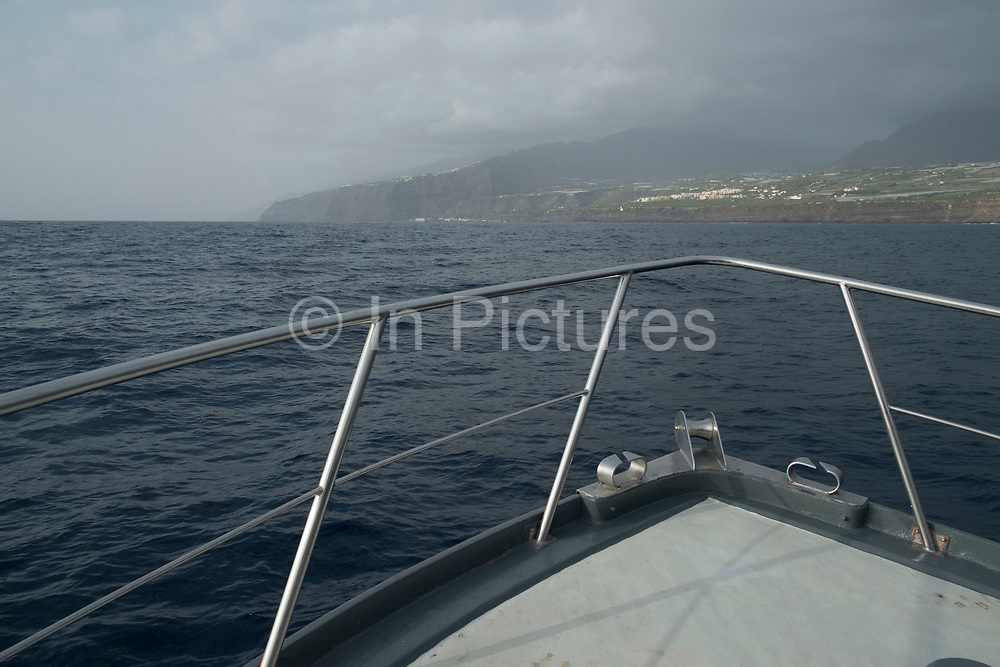 View from the bow of a boat out at sea on the Atlantic Ocean looking towards the volcanic coastline near Tazacorte in La Palma, Canary Islands, Spain. La Palma, also San Miguel de La Palma, is the most north-westerly Canary Island in Spain. La Palma has an area of 706km2 making it the fifth largest of the seven main Canary Islands.