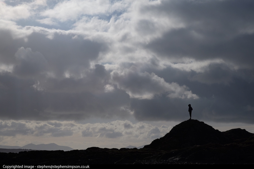 © Licensed to London News Pictures. 14/02/16. Anglesey. UK.  A man stands under clouds on Rhosneiger beach in Anglesey, North Wales. Photo credit : Stephen Simpson/LNP