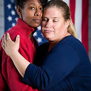 Tra-c Cooper-Harris, in red , an Army veteran, and her wife, Maggie. Tra-c and Maggie successfully challenged the Defense of Marriage Act (DOM) which excluded survivor benefits to Maggie. The two are now legally married in all 50 states after the Supreme Court of the United States ruled that gay marriage is a constitutional right.