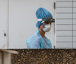 © Licensed to London News Pictures. 13/02/2020. London, UK. Hospital staff in full protective gear and testing kit at the back of an ambulance a St Thomas's Hospital this morning as the first London Coronavirus victim is currently being treated there. Photo credit: Alex Lentati/LNP