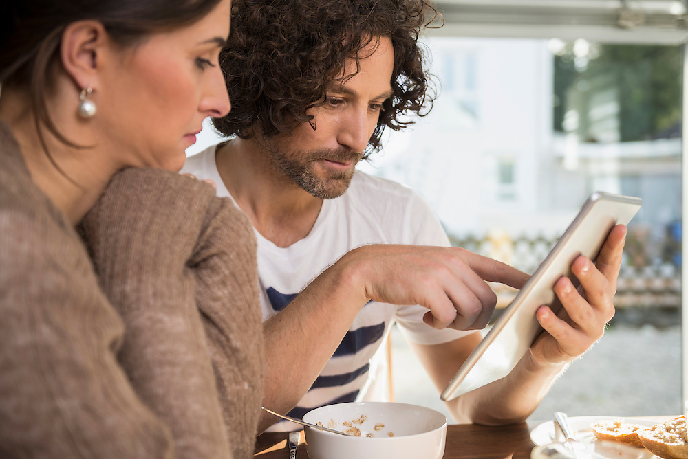Mid adult couple using a digital tablet, Munich, Bavaria, Germany
