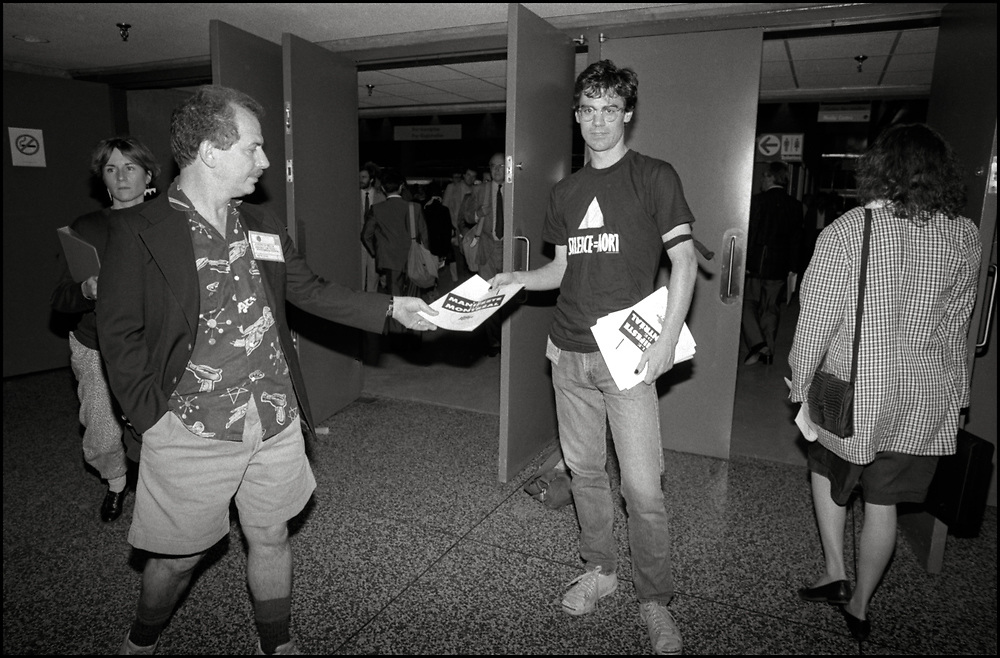 """Walter Armstrong of ACT UP NY handed out copies of the """"Montreal Manifesto,"""" a declaration of human rights for people with AIDS and HIC+V infection, to attendees at the Fifth International AIDS Conference in Montreal. <br /> <br /> ACT UP NY stormed the Fifth International AIDS Conference in Montreal, at the time a members-only event for doctors and HIV/AIDS researchers. They took over seats reserved for dignitaries, and released their first Treatment and Data report calling for speedier access to AIDS drugs."""
