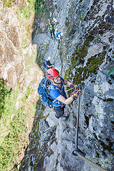 Group of people climbing rock face via ferrata towards Stuibenfall Waterfall, Otztal, Tyrol, Austria