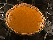 Freshly baked pumpkin pie cooling on the stove