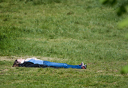 © Licensed to London News Pictures. 14/04/2020. London, UK. A member of the public relaxing in the sun on Primrose Hill in North London, during a pandemic outbreak of the Coronavirus COVID-19 disease. The public have been told they can only leave their homes when absolutely essential, in an attempt to fight the spread of coronavirus COVID-19 disease. Photo credit: Ben Cawthra/LNP