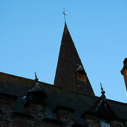 A turret and roof of an historic building in Burg Square, Bruges, stands out against the lightening blue sky before dawn.