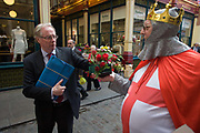 St George in full regalia hands out free red roses to Londoners in Leadenhall Market in the City of London, on England's national St George's Day the 23rd April. On the day that the English celebrate their patron saint, many gather in the City's main covered marketplace to wear red and drink to thoughts of nationalism. Saint George was born in Lydda, Syria Palaestina, a soldier in the Roman army and was later venerated as a Christian martyr. Nowadays his ideal has been used by the far-right and here, during the 2015 General Election, as political point-scoring.