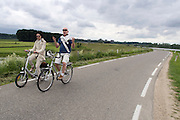Een man en vrouw fietsen over de dijk in de Ooijpolder bij Nijmegen. De vrouw rijdt op een elektrische vouwfiets.<br /> <br /> A man and woman are cycling on the dike at the Ooijpolder near Nijmegen. The woman is riding an electrical folding bike.