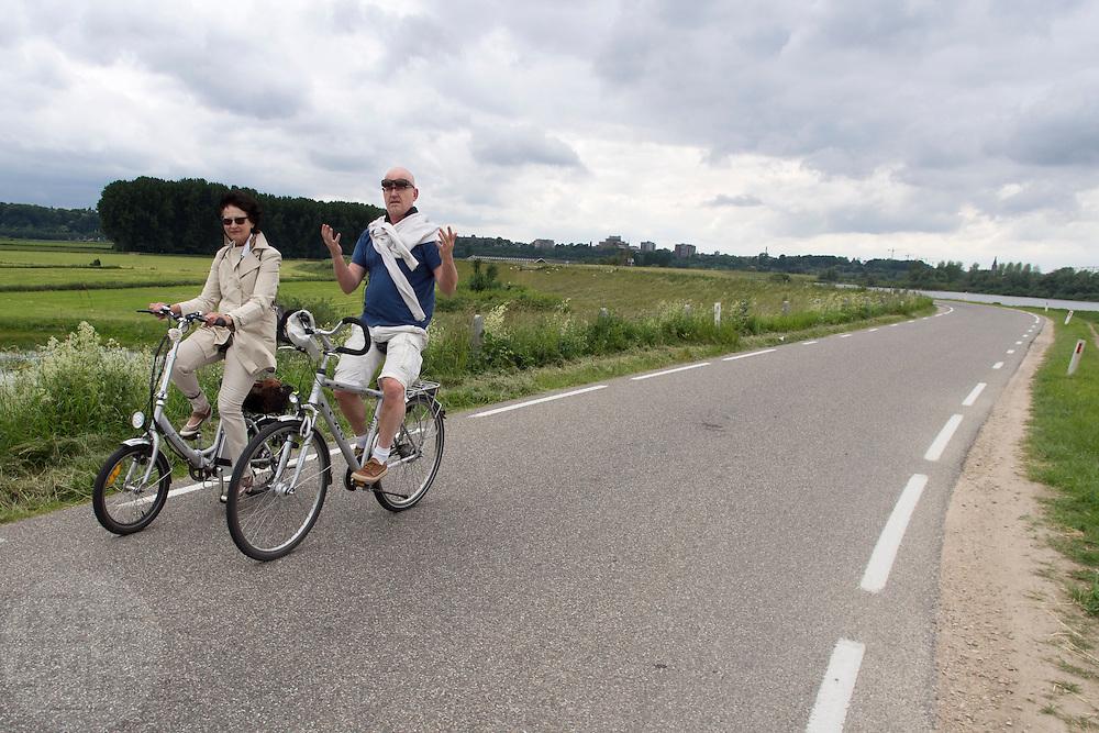Een man en vrouw fietsen over de dijk in de Ooijpolder bij Nijmegen. De vrouw rijdt op een elektrische vouwfiets.<br /> <br /> A man and woman are cycling on the dike at the Ooijpolder near Nijmegen. The woman is riding an electrical folding bike.