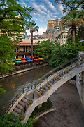 "The San Antonio River Walk (also known as Paseo del Río) is a network of walkways along the banks of the San Antonio River, one story beneath the streets of Downtown San Antonio, Texas, USA. Lined by bars, shops and restaurants, the River Walk is an important part of the city's urban fabric and a tourist attraction in its own right.<br /> Today, the River Walk is an enormously successful special-case pedestrian street, one level down from the automobile street. The River Walk winds and loops under bridges as two parallel sidewalks lined with restaurants and shops, connecting the major tourist draws from the Alamo to Rivercenter Mall, to the Arneson River Theatre, to Marriage Island, to La Villita, to HemisFair Park, to the Tower Life Building, to the San Antonio Museum of Art, and the Pearl Brewery. During the annual springtime Fiesta San Antonio, the River Parade features flowery floats that ""float"" down the river."